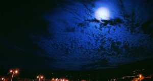 the night sky with full moon illuminateing the clouds